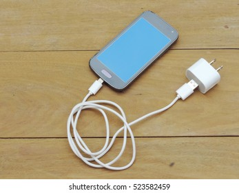 smartphone with white charger adapter on wood background.
