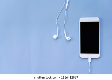 Smartphone and White Earphones on Blue Background Top View with Copy Space
