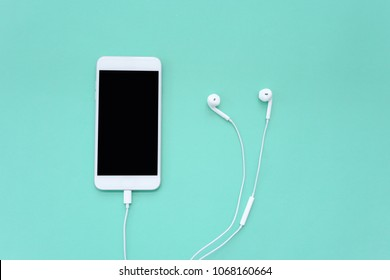 Smartphone with White Earphones on Turquoise Background Top View