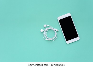 Smartphone and White Earphones on Turquoise Background Top View
