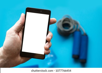 Smartphone with white screen in mans hand and sports equipment on blue background.