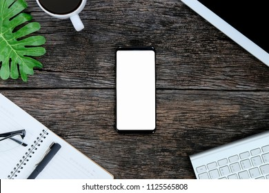 Smartphone white screen on wooden table and supplies with keyboard and coffee, Top view with copy space.