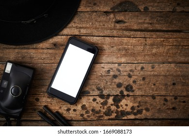 Smartphone white screen on wooden table.