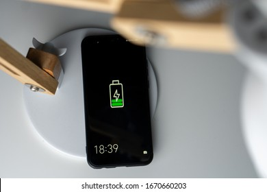 Smartphone wireless charging lamp, on induction charger. Wooden lamp on a white desk. Modern technologie