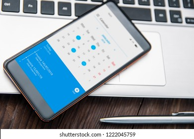 Smartphone witch notch lies on the desk with calendar application that remind about invoices to pay.