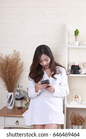 Smartphone woman using app on mobile smart phone smiling happy.. Asian Beauty