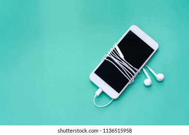 Smartphone Wrapping Round with Earphones on Turquoise Background Top View