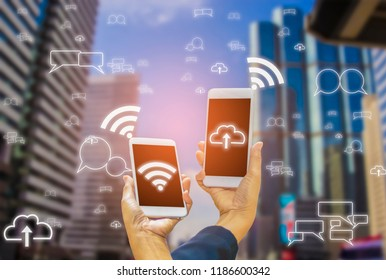 Smartphones in hands of  wifi and cloud symbols, with backgrounds as city landscapes, concepts for wireless connectivity and convenient communications, IOT (Internet of Thing)