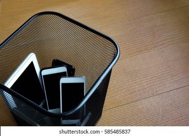 Smartphones in trash bin with copy space