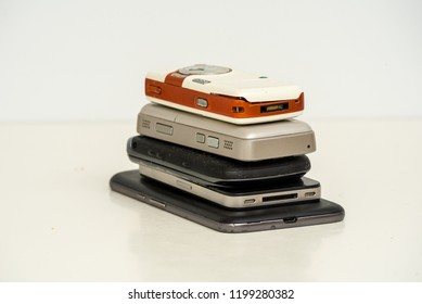 smartphones (used and broken) on white table, white background