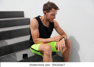 Smartwatch runner man checking progress on smart fitness sport watch during running break after hiit stairs cardio workout training. Athlete using online app on wearable device. Active lifestyl.