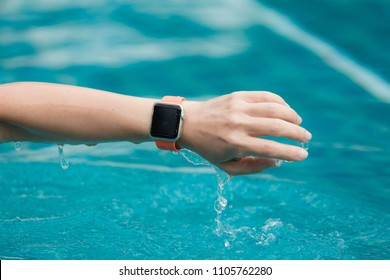 Smartwatch woman relaxing on swimming pool wearing smart wrist watch for activity tracker for an active lifestyle