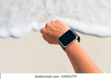 Smartwatch woman wearing fitness smart watch looking at screen on beach. POV closeup of wrist and hand on summer travel holiday person training run on beach vacation.