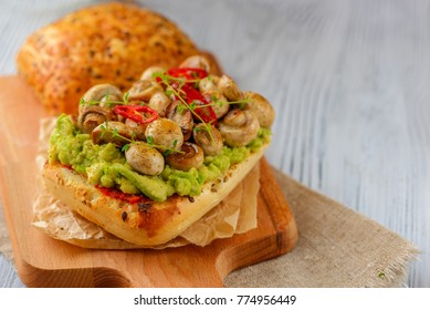 Smashed avocado, mushrooms and chili pepper whole grain sandwich. Decorated with thyme