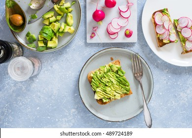 Smashed avocado on whole grain toast to make avocado and radish sandwiches