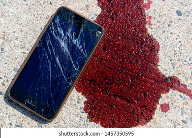 A smashed and broken mobile phone by a puddle of blood on a sidewalk. The screen on the cell phone is broken and shattered. The blood appears to be fresh. The phone is unidentifiable.