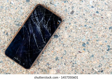 A smashed and broken mobile phone lying on a concrete sidewalk. The screen on the cell phone is broken and shattered. The phone is unidentifiable.