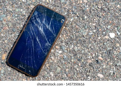 A smashed and broken mobile phone lying on an asphalt road. The screen on the cell phone is broken and shattered. The phone is unidentifiable.