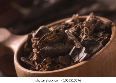 Smashed carob pods on a wood with cup