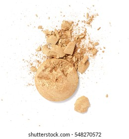 Smashed and cracked golden eye shadow isolated on a white background.