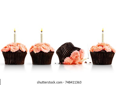 Smashed cupcake in row of cupcakes with candles isolated on white