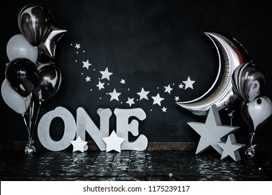 Smashed first birthday white cake with stars and one candle for little baby boy and decorations. Black background. Big silver letters ONE, silver stars and different balloons