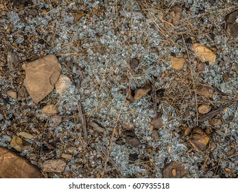 Smashed glass spread over the ground between rocks