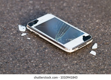 Smashed mobile phone / cell phone / smartphone lying on the pavement with copy space