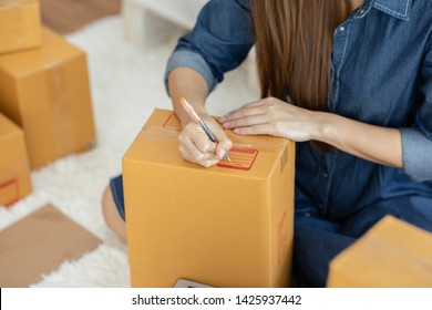 SME entrepreneur of Young women working with laptop and writing customer address for send order Online shopping at home,Cheerful and Happy with box for packaging in home,Startup and Freelance Concept