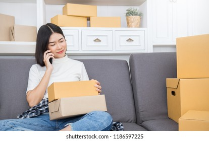 SME freelance woman working at home office, Young Asian small business owner using smartphone, online shopping marketing pack delivery, SME e-commerce telemarketing warehouse technology concept