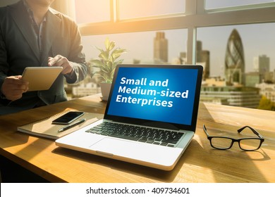 SME or Small and medium-sized enterprises Thoughtful male person looking to the digital tablet screen, laptop screen,Silhouette and filter sun