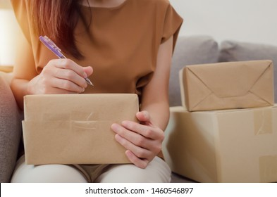 SME startup. young entrepreneur woman working and writing customer address on packaging parcel box for send order to customer at home office, shopping online, small business owner and delivery concept
