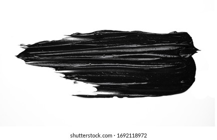 Smear of a black charcoal mask on white isolated background. Smudge texture brush stroke.