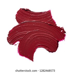 Smear of burgundy red lipstick or acrylic paint isolated on white background