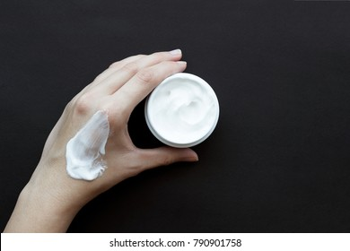 Smear cream on woman hand. Lotion for face or body. Skin care.