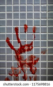 Smeared fresh bloody handprint or bloodstains with streaks on bathroom tiles wall. Horror halloween or Violent Crime or Homicide murder or Domestic violence concept.