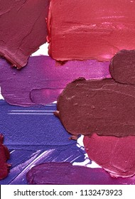 Smears of different colors are made with various lip gloss isolated on a white background. Texture of multi-colored strokes of various make-up cosmetics on a white background