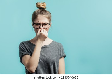 Smells bad, awful odor. Young student girl with hair bun in casual t-shirt squeezing nose with fingers, looking in camera with disgust expression, eager to slip away from bad smell indoors
