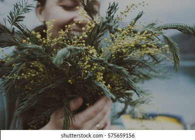 Smells spring. Bouquet of mimosa in womans hands in the evening near the sea