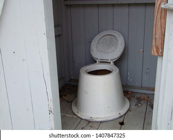Smelly, nasty, vile, dirty old wooden outhouse.