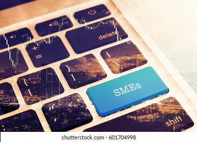 SMEs (SMALL AND MEDIUM-SIZED ENTERPRISES): Close up green button keyboard computer. Vintage Effects. Digital Business and Technology Concept.