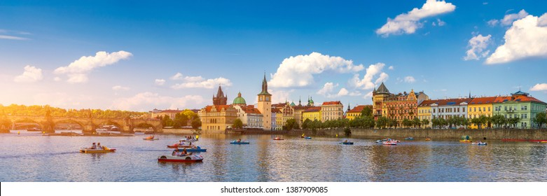 Smetanovo Embankment with Charles Bridge and boats on Vltava river, Prague, Czech Republic. Embankment of the Vltava river in Prague, the capital of Czechia.