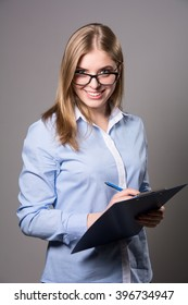 Smiele young woman in glasses standing and holding clipboard and pen over grau background