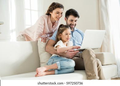 smiing parents and focused daughter using laptop at home