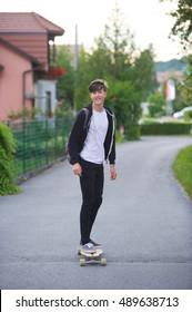 Smiing teenager longboarding in a suburban setting.