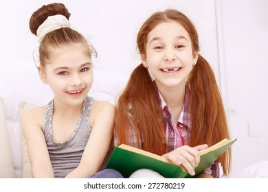 Smile is all you need. Two cute little girls sitting reading book and frankly smiling.