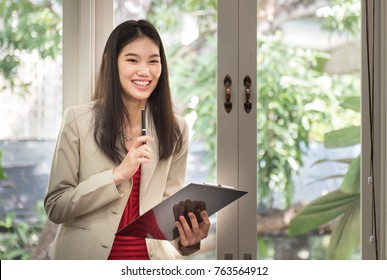 Smile of Beautiful Asian Businesswoman stand near the window. in office.  business successful concept.