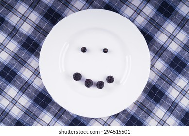 Smile of berries on a white plate