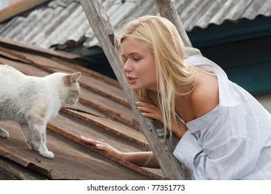 Smile blondie at the stairs in the village with cat