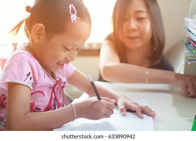 Smile child daughter happily study with her mother at home.